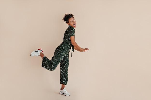 Jolie femme en salopette verte debout sur une jambe