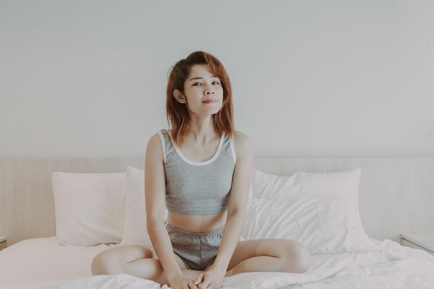 Jolie femme se détendre après le réveil en vacances d'été dans la chambre