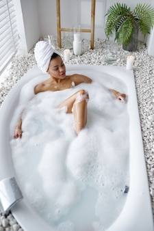 Jolie femme se détendre dans le bain avec de la mousse. personne de sexe féminin dans la baignoire, soins de beauté et de santé au spa, traitement de bien-être dans la salle de bain, cailloux et bougies sur fond