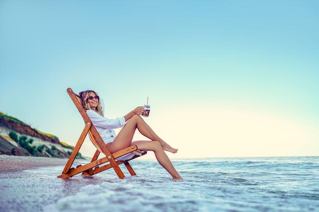 Jolie femme se détendre sur une plage de transats et boit de l'eau gazeuse. concept de vacances d'été