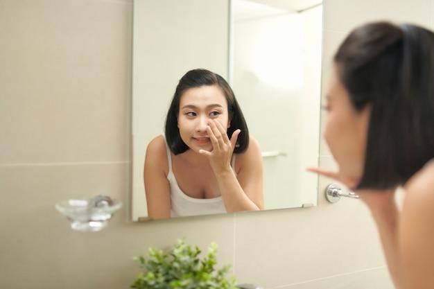 Jolie femme à se laver dans la salle de bain après avoir appliqué un masque