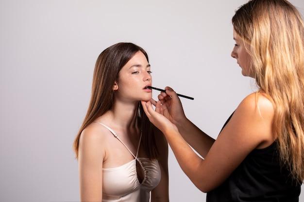 Jolie femme se maquiller par un professionnel