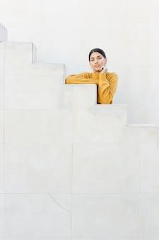 Jolie femme se penchant sur les marches en regardant la caméra