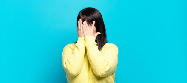 Jolie femme se sentant effrayée ou gênée, furtivement ou espionnant avec les yeux à moitié couverts de mains