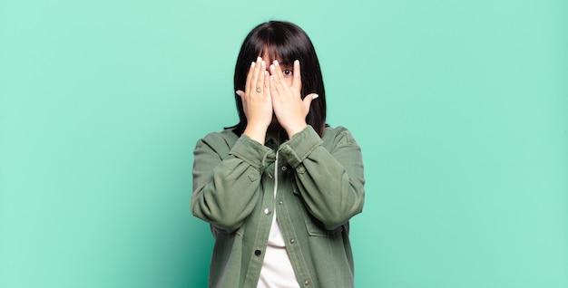 Jolie femme se sentant effrayée ou gênée, regardant ou espionnant avec les yeux à moitié couverts de mains
