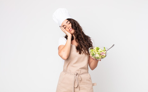 Jolie femme se sentant ennuyée, frustrée et somnolente après un fastidieux portant un tablier et tenant une salade