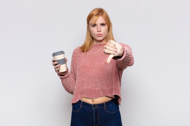 Jolie femme se sentant fâchée, en colère, agacée, déçue ou mécontente, montrant les pouces vers le bas avec un regard sérieux