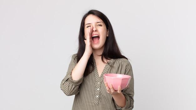 Jolie femme se sentant heureuse, donnant un grand cri avec les mains à côté de la bouche tenant un bol de pot vide. agent assistant avec un casque