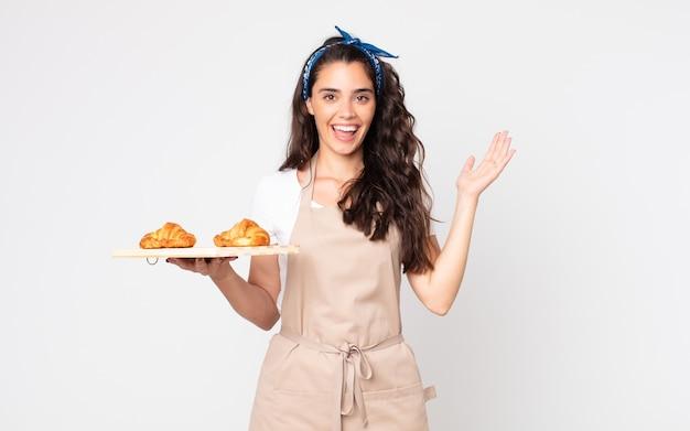 Jolie femme se sentant heureuse et étonnée de quelque chose d'incroyable et tenant un plateau de croissants