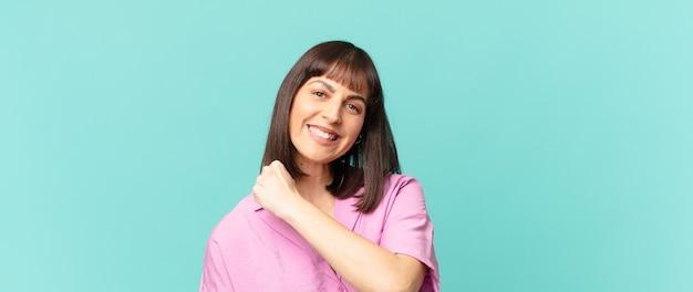 Jolie femme se sentant heureuse, positive et réussie, motivée face à un défi ou célébrant de bons résultats