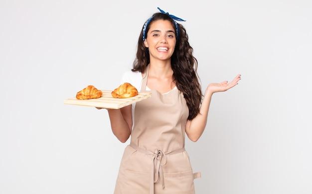 Jolie femme se sentant heureuse, surprise de réaliser une solution ou une idée et tenant un plateau de croissants