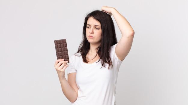 Jolie femme se sentant perplexe et confuse, se grattant la tête et tenant une barre de chocolat