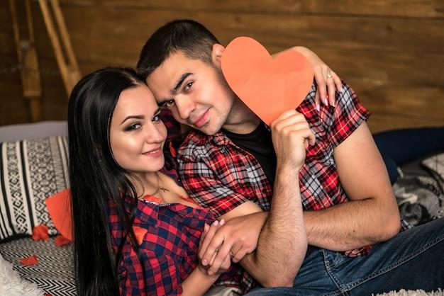 Jolie femme se trouvant près de bel homme tenant coeur de papier rouge souriant