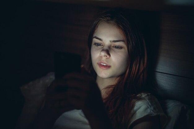 Jolie femme se trouve dans son lit avec un téléphone dans ses mains à la relaxation de la dépendance de nuit.
