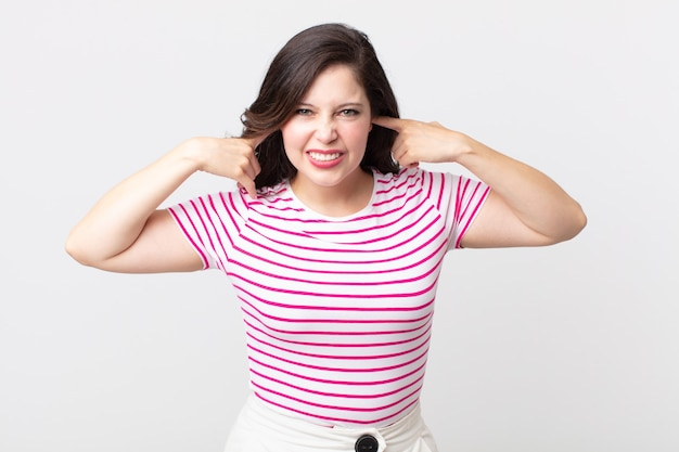 Jolie femme semblant en colère, stressée et agacée, couvrant les deux oreilles à un bruit assourdissant, un son ou une musique forte