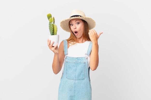 Jolie femme semblant étonnée d'incrédulité et tenant une plante décorative de cactus