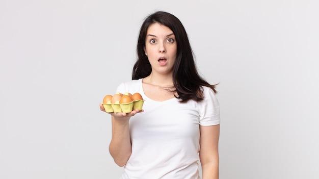 Jolie femme semblant très choquée ou surprise et tenant une boîte à œufs