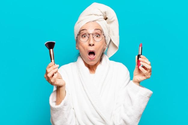 Jolie femme senior après la douche maquillant et portant un peignoir