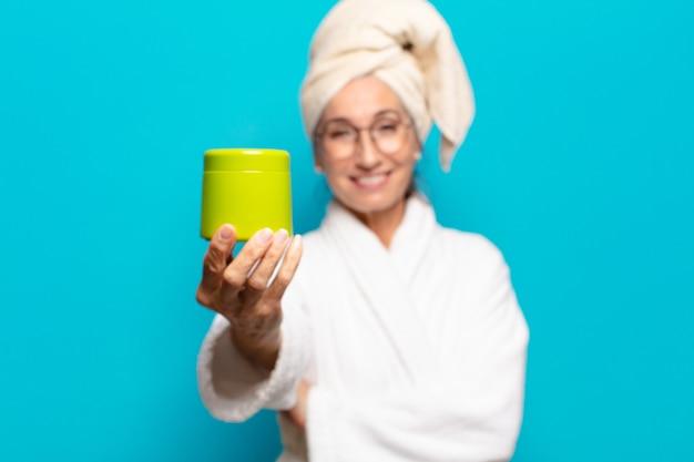 Jolie femme senior après la douche en peignoir. concept de produits de nettoyage du visage ou de douche