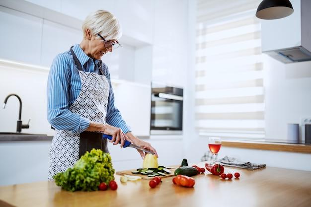 Jolie femme senior blonde en tablier debout dans la cuisine à la maison et couper le poivron jaune