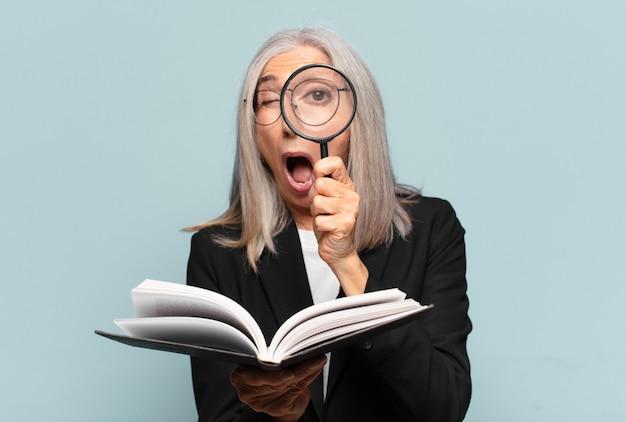 Jolie femme senior avec un livre et une loupe. concept de recherche