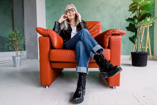 Jolie femme senior moderne souriante avec de longs cheveux gris étoilés, portant une veste en cuir à la mode et un jean, assis dans une chaise confortable et un téléphone parlant avec un ami