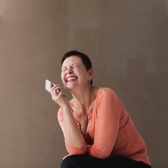 Jolie femme senior avec téléphone en riant