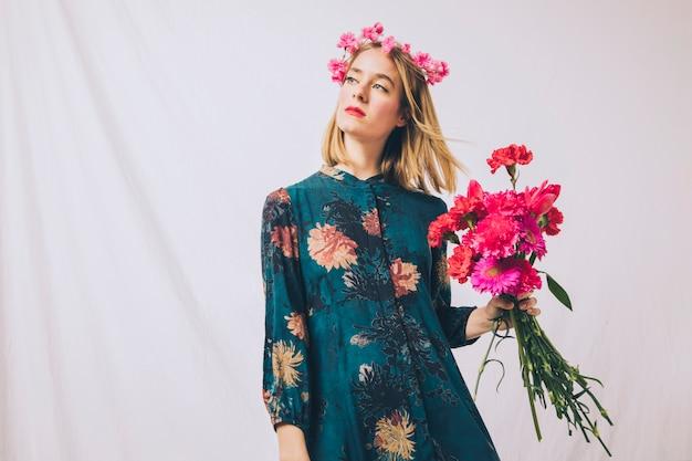 Jolie femme sensuelle avec guirlande sur la tête et bouquet de fleurs