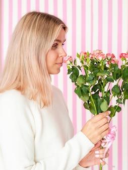 Jolie femme sentant le bouquet de fleurs