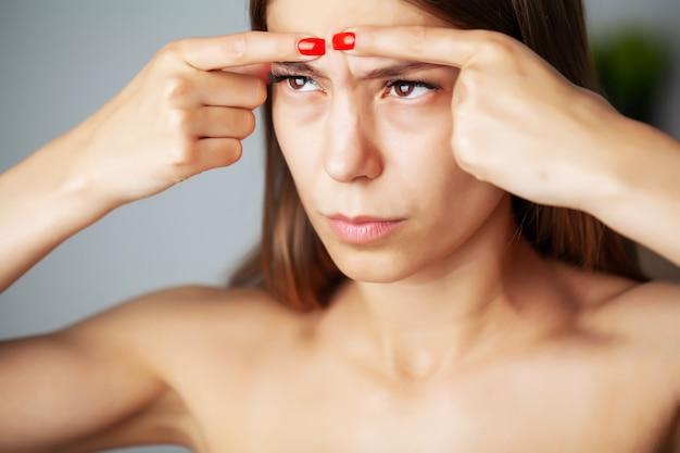 Jolie femme a serré un bouton sur son visage devant un miroir dans la salle de bain