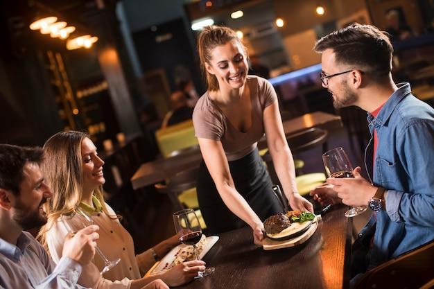 Jolie femme serveur servant un groupe d'amis avec de la nourriture dans le restaura