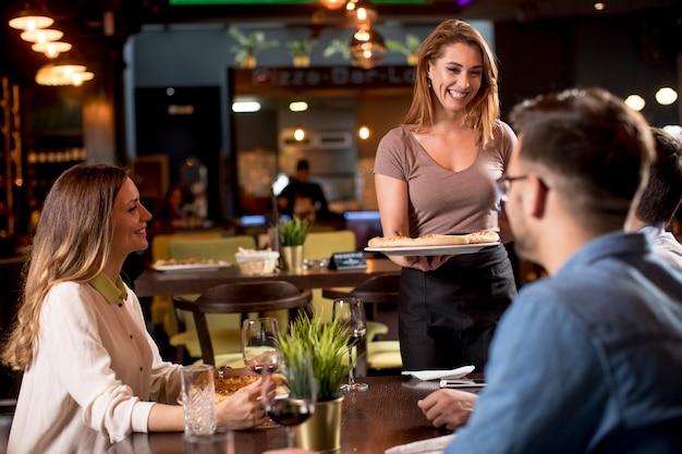 Jolie femme serveur servant un groupe d'amis avec de la nourriture dans le restaurant