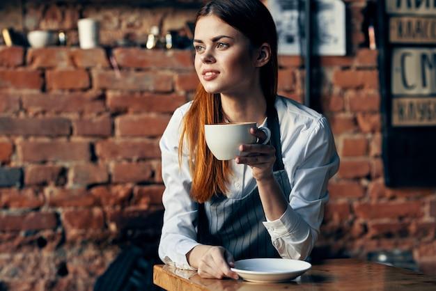 Jolie femme serveur tenant mug mur de briques restaurant
