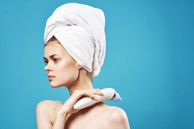 Jolie femme avec une serviette aux épaules nues sur le masseur de soins spa de la tête