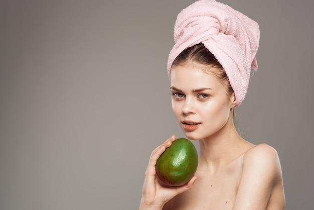 Jolie femme avec une serviette rose sur la tête de la mangue épaules nues vitamines