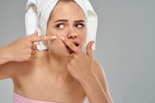 Jolie femme avec une serviette sur la tête fait sortir des boutons sur son visage