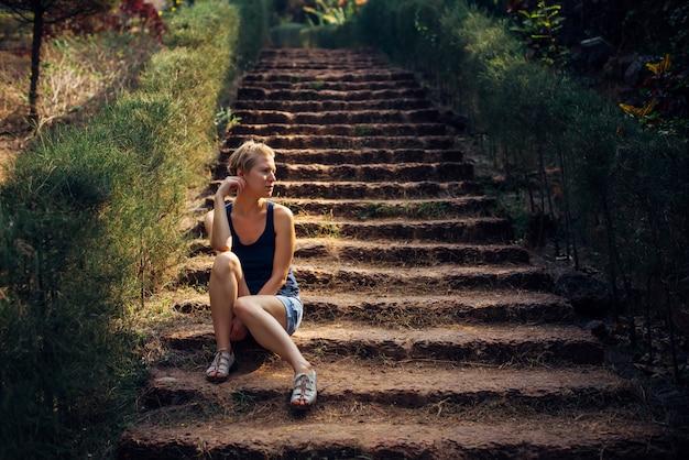 Jolie femme en short en jean, assis sur l'escalier dans le parc d'été.