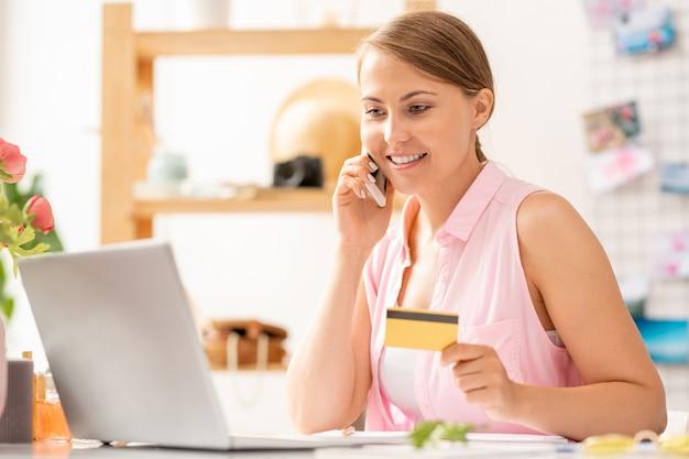 Jolie femme avec smartphone indiquant le nombre de carte de crédit au consultant de la boutique en ligne tout en passant commande sur le net