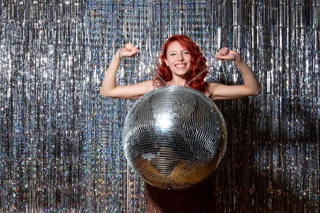 Jolie femme en soirée disco se réjouissant souriant sur des rideaux lumineux