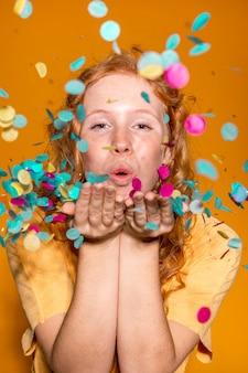 Jolie femme soufflant des confettis