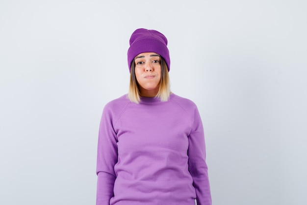 Jolie femme soufflant des joues en pull, bonnet et semblant perplexe, vue de face.