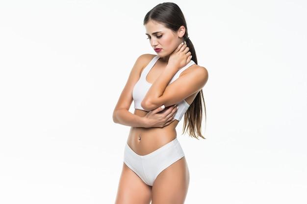 Jolie femme souffrant de douleurs au coude isolé sur mur blanc