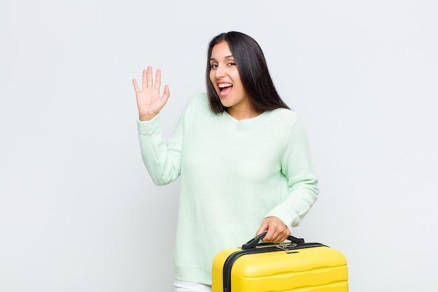 Jolie femme souriant joyeusement et gaiement, agitant la main, vous accueillant et vous saluant, ou vous disant au revoir