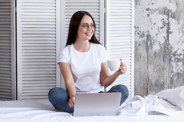 Jolie femme souriante à l'aide de tablette numérique à la maison