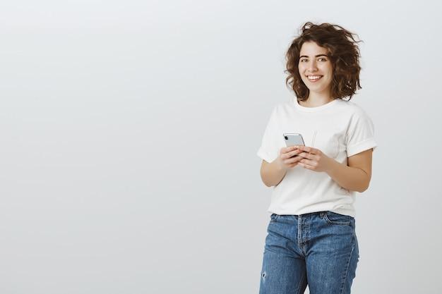 Jolie femme souriante à l'aide de téléphone portable, sms, défilement des médias sociaux