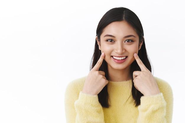 Jolie femme souriante aux cheveux courts foncés pointant sur les joues et souriant, recommande d'utiliser un produit de soin de la peau ou des cosmétiques pour la peau, mur blanc debout