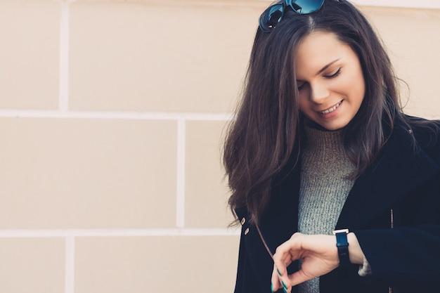 Jolie femme souriante aux cheveux longs en manteau noir vérifie l'heure