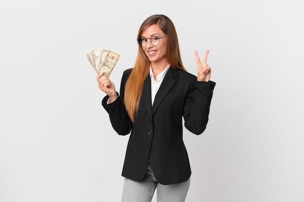 Jolie femme souriante et ayant l'air heureuse, gesticulant la victoire ou la paix. concept d'entreprise et de dollars