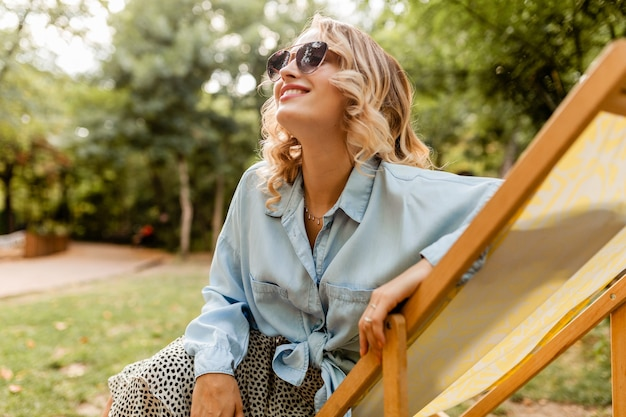 Jolie femme souriante blonde assise dans une chaise longue en tenue élégante