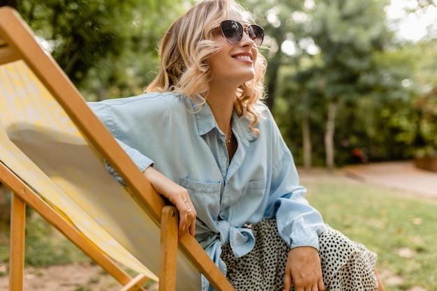 Jolie femme souriante blonde assise dans une chaise longue en tenue d'été